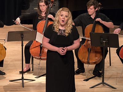 Young woman on stage with cellists.
