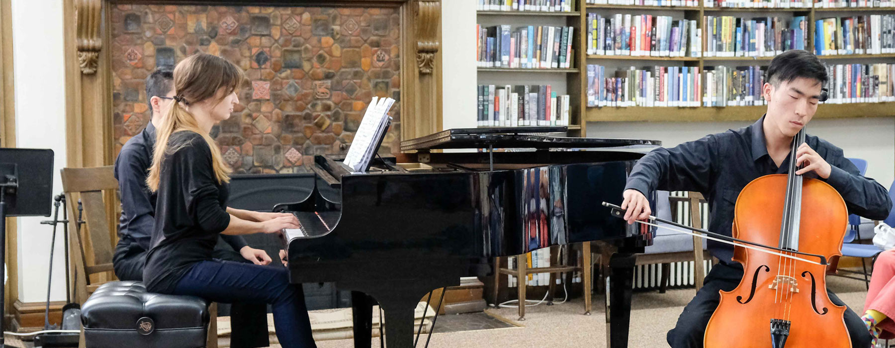 Young pianist and cellist performing in library.
